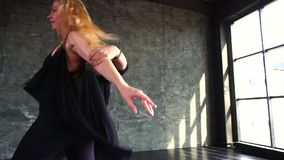 Professional dancers dancing in the studio. A pair of dancers beautifully dance against the background of a large window. Professional dancers dancing in the stock footage
