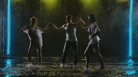 Professional dancers perform salsa elements in a dark smoky studio. Silhouettes of three bodies in the rain moving in