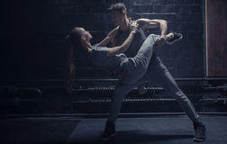 Professional dancers performing in the dark lighted room Stock Photo