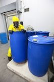 Professional dealing with barrels toxic substance. Fully protected in yellow uniform,mask,and gloves professional dealing with barrels with toxic substance stock photography