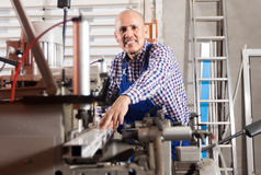 Professional debonair worker toiling on a machine in PVC shop Royalty Free Stock Photos