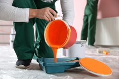 Professional decorator with bucket of paint indoors. Home repair service stock photo