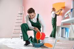 Professional decorator with bucket of paint. Home repair service royalty free stock photos
