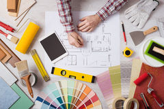 Professional decorator working at desk. Professional decorator drawing on a house project with work tools, painting rollers and color swatches all around, top Stock Photos