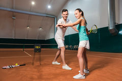 Professional delighted instructor teaching woman to play tennis Royalty Free Stock Photos