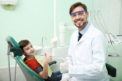 Professional dentist and happy little patient in clinic stock images