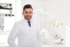 Professional dentist at his clinic. Horizontal portrait of a handsome hispanic male dentist posing at his clinic smiling to the camera joyfully copyspace Stock Images