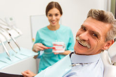 Professional dentist office. Elderly men on a review of a dentist, sitting in a chair stock photo