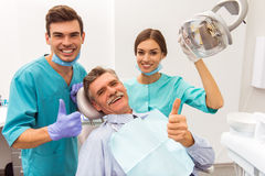 Professional dentist office. Young doctor dentist and his assistant, elderly patient showing thumb up, smiling and looking at the camera stock photos