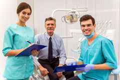 Professional dentist office. Young doctor dentist and his assistant recording in the documents. An elderly men sitting in the dental chair royalty free stock photo