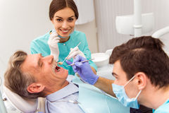 Professional dentist office. Young dentist and his assistant treating elderly man royalty free stock photo