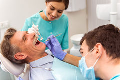 Professional dentist office. Young dentist and his assistant treating elderly man royalty free stock photos