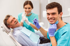 Professional dentist office. Young dentist and his assistant treating elderly man stock photo