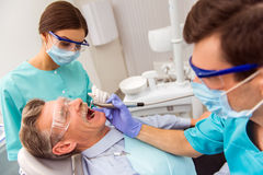 Professional dentist office. Young dentist and his assistant treating elderly man stock images