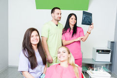 Professional dentist team and happy patient. In dental office stock photo