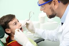 Professional dentist working with little patient in clinic royalty free stock image