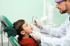 Professional dentist working with little patient in clinic royalty free stock photography