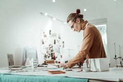 Professional designer from a fashion studio in a brown garment looking concentrated. Working hard. Professional designer from a fashion studio wearing a brown stock photo