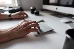 Professional designer man working at the computer. Closeup of male hands  and white desktop. Professional designer man working at the computer. Closeup of male royalty free stock image