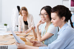 Professional designers discussing a dress sketch. Sharing ideas. Two pretty young designers sitting at the table and discussing a sketch for a new dress while Royalty Free Stock Image