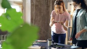 Professional designers are making flat lay by placing photos, coffee and camera on table and shooting with smartphone. Women are arranging things on desk, then stock footage