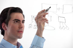 Professional development. Young, handsome professional working on a flow diagram on on a see-through board on white background. Focus on man royalty free stock photo