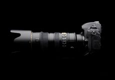 Professional digital photo camera. With zoom lens on black background Stock Images