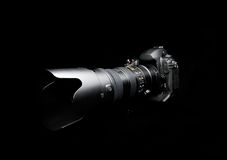 Professional digital photo camera. With zoom lens on black background Royalty Free Stock Images