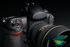 Professional digital photo camera. With zoom lens on black background Stock Photos