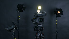 Professional digital video camera, camcoder isolated on black background in tv srudio. stock footage
