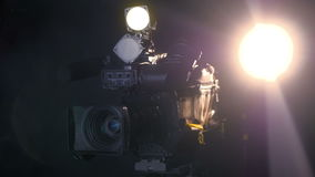 Professional digital video camera, camcoder isolated on black background in tv srudio. stock video