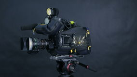 Professional digital video camera, camcoder isolated on black background in tv srudio. stock video footage