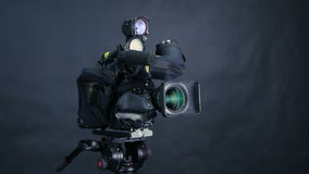 Professional digital video camera, camcoder isolated on black background in tv srudio. 4K stock footage