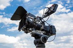 Professional digital video camera. Professional video camera on a tripod against the blue sky Stock Photo