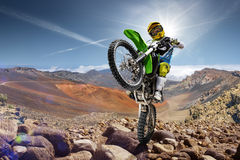 Professional dirt bike rider doing wheely. On the top of vulcan Stock Images