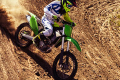 Professional dirt bike rider. Motocross rider in action accelerating the motorbike on the race track stock image