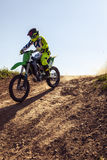 Professional dirt bike rider. Motocross rider in action accelerating the motorbike on the race track stock photography