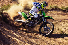 Professional dirt bike rider. Motocross rider creates a large cloud of dust and debris stock image