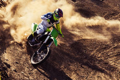 Professional dirt bike rider. Motocross rider creates a large cloud of dust and debris Royalty Free Stock Photos