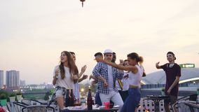 Professional DJ is working at cool rooftop party with joyful young men and women dancing and having fun enjoying music. Leisure and summertime in big city stock video footage
