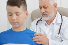 Professional doctor examining boy`s back and spine. stock photography
