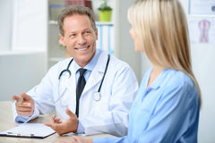 Professional doctor examining his patient. In a good mood. Pleasant overjoyed smiling professional doctor holding pen and sitting at the table while talking with Stock Images