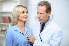 Professional doctor examining his patient Stock Photos