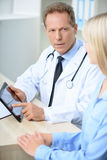 Professional doctor examining his patient. Look here. Pleasant serious professional doctor sitting at the table and holding laptop while talking with patient Stock Images