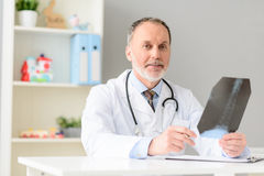 Professional doctor holding radiogram. Everything seems to be in order here. Mature male doctor smiling while looking at x-ray image at his office Stock Photos