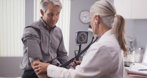 Professional doctor measuring senior man's blood pressure Stock Photos