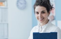 Professional doctor posing in the office. Smiling professional young doctor posing in the office and looking at camera, she is holding a clipboard stock images
