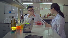 Professional doctor teaching intern in medical laboratory. Adult man with assistant research blood test in lab. Woman telling her observation holding digital stock video