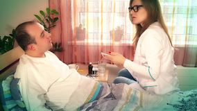 Professional doctor woman in glasses examining her patient man in hospital ward stock video footage