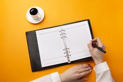 Professional doctor writing medical records in a notebook with coffee cup stock image